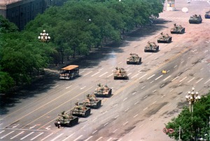 A lone demonstrator stands down a line of Chinese PLA tanks along Changan Ave. near the edge of Tiananmen Square. Beijing 1989. © Charlie Cole